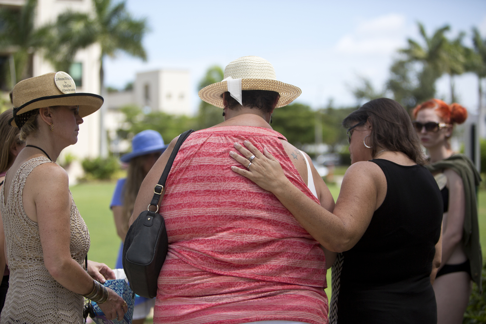 Tamara Paquette, left, and Melody Klein, right, console Tamara Gossard, center, as she reads the victim's letter at the Stanford Rape Protest at Mercato on Saturday, June 11, 2016 in Naples, Florida.