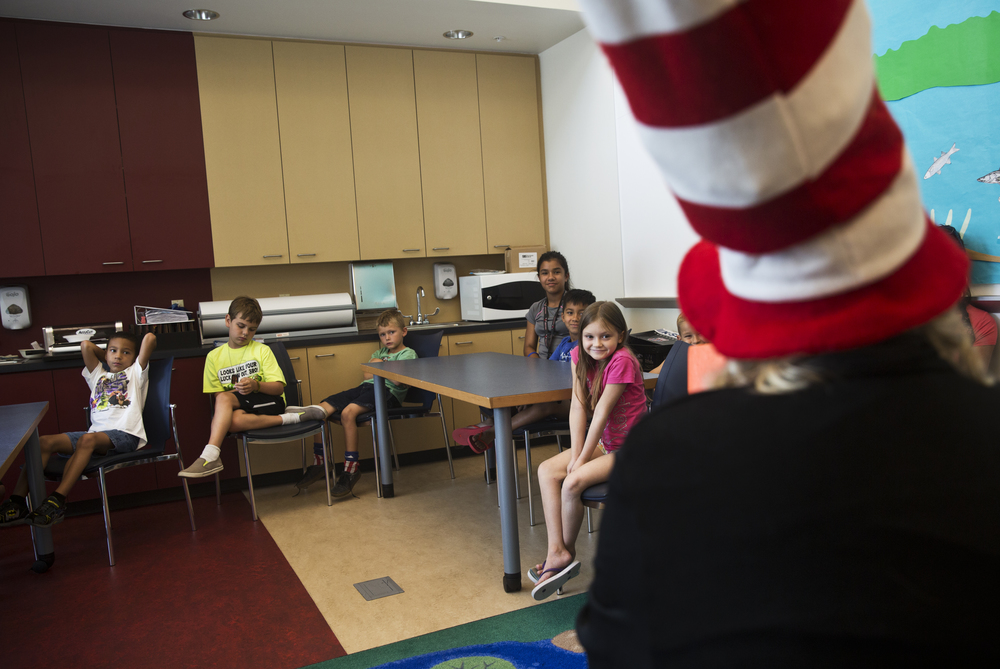"""Haylee Kelley, 7, right, of Naples, listens in excitement to a reading of Dr. Seuss' Green Eggs and Ham at the Golden Gate Library on June 21, 2016. The reading, lead by Connie Bettinger-Hennink dressed as Dr. Seuss' Cat in the Hat, was a part of the Collier County Public Libraries """"On Your Mark, Get Set, Read"""" summer programs."""
