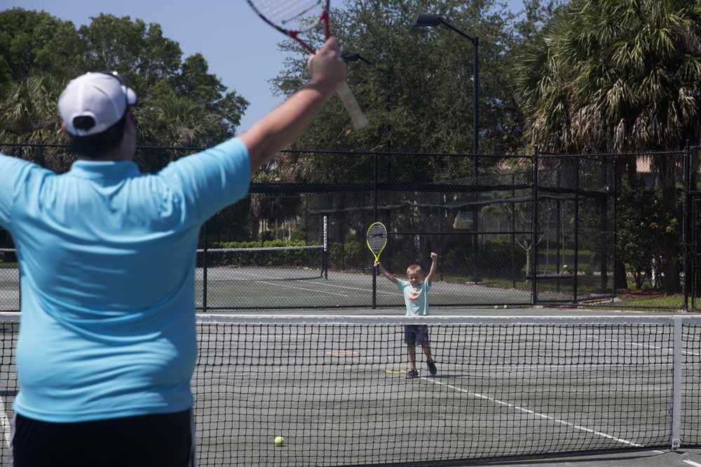 Ronald Kanova, 5, celebrates with his coach John Irish, 27, after winning a game during the Naples Tennis Academy Summer Camp on Tuesday, June 14, 2016 at Pelican Bay Community Park in Naples Florida. The summer camp runs from June 7 thru August 16 and teaches the fundamentals for beginners and recreational level players.