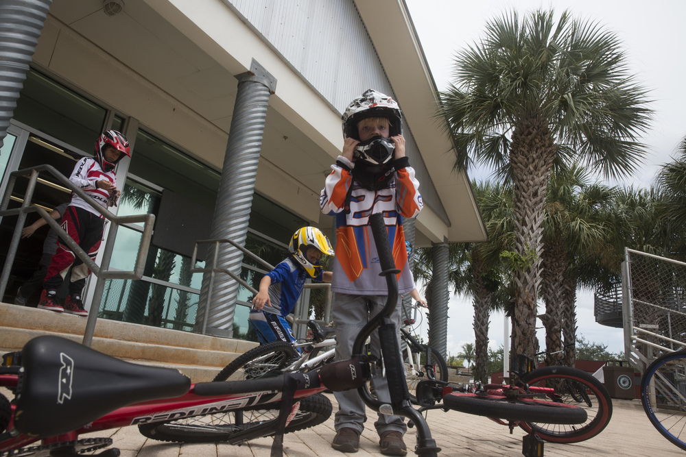 Brennan Brewer, 7, of Naples, puts on his helmet during BMX camp at the Golden Gate Wheels skate and BMX park on July 12, 2016. The camp teaches beginner BMX riders the fundamentals of racing.
