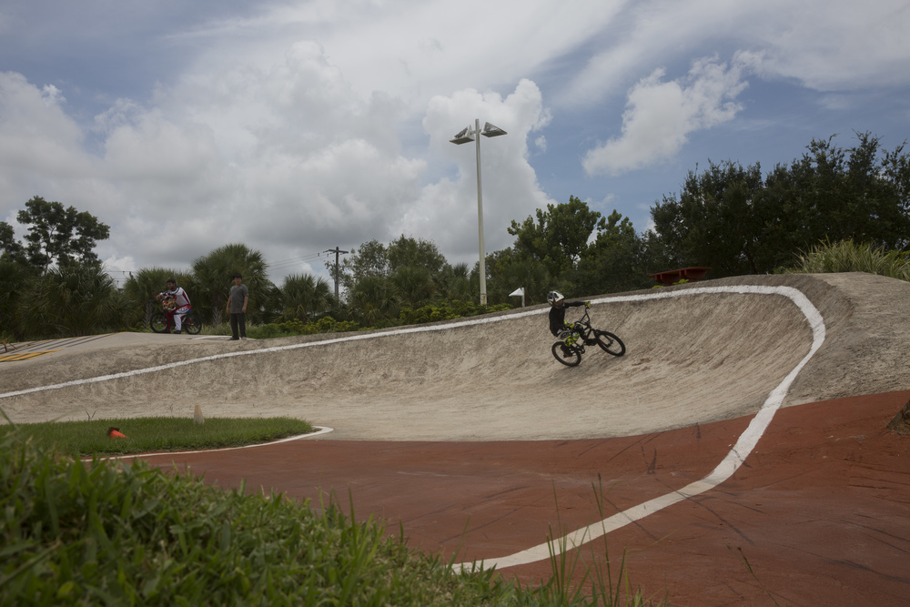 Logan Bartley, 9, of Naples, rounds the bend during BMX camp at the Golden Gate Wheels skate and BMX park on July 12, 2016.