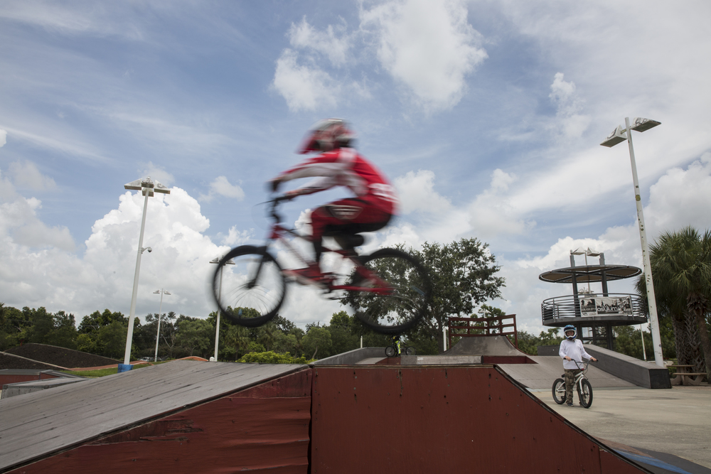 Riley Olsovsky, 11, right, watches Peter Backus, 10, both of Naples, perform a jump during BMX camp at the Golden Gate Wheels skate and BMX park on July 12, 2016.