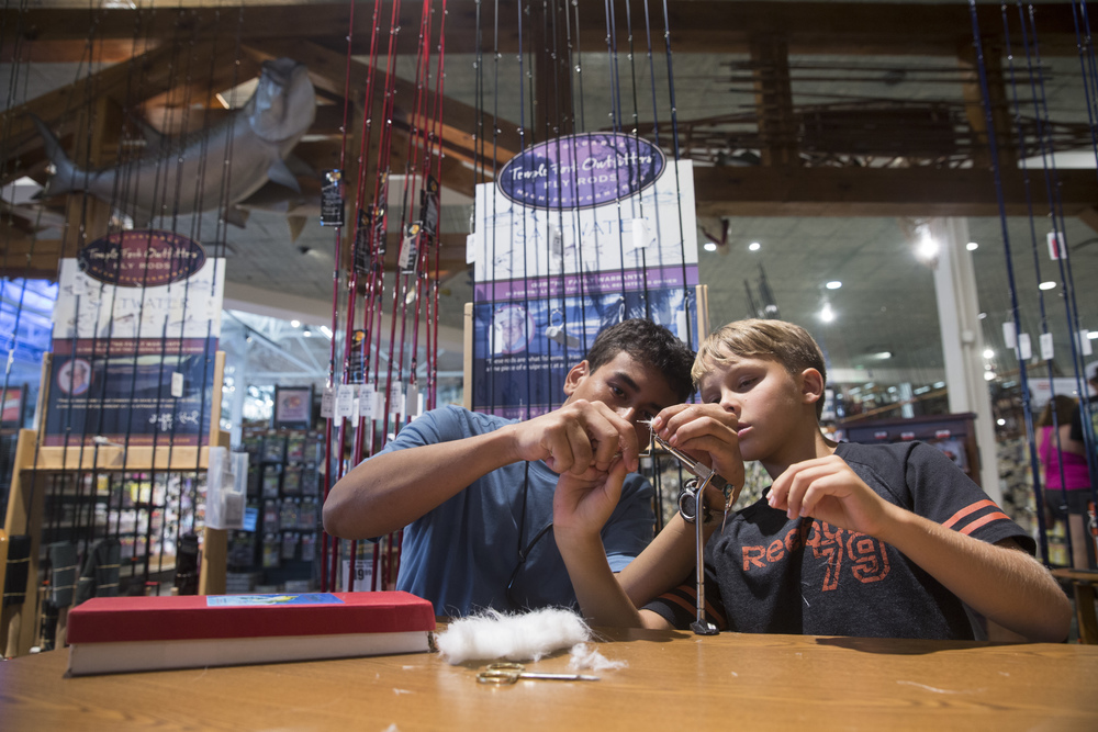 Chris Romero, 18, left, helps Jack Puskaric, 11, with his fly tying on July 6, 2016 at the Bass Pro Shops in Fort Myers, Florida. Fly Casting Instructor Joe Mahler hosts free family fly tying and nest casting classes at the shop every Wednesday night.