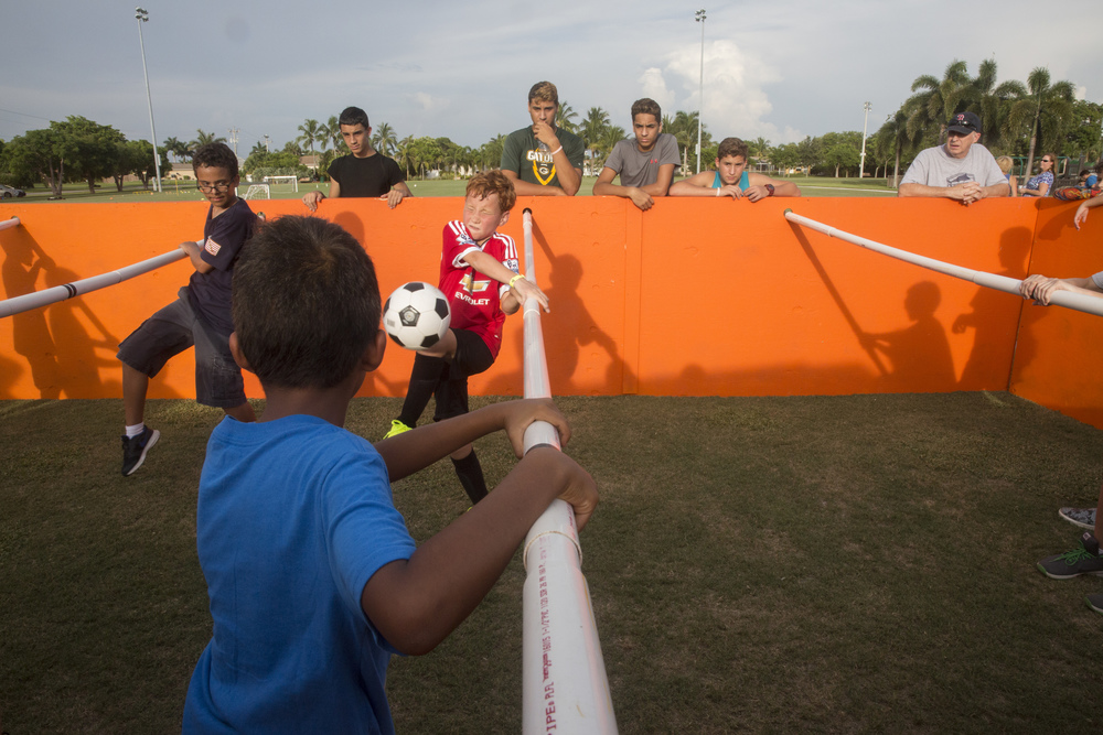 Ivan Harrison, 10, center, of Naples, reacts as he's hit by the ball in a human foosball game during the Hot Summer Nights event in Mackle Park on July 8, 2016 on Marco Island, Florida. Hot Summer Nights is a free family fun event hosted by the Collier County Sheriff's Office at a different community park every Friday night in July from 6-9 PM. Activities include a rock wall, a bounce house, a human foosball arena, karaoke and more.