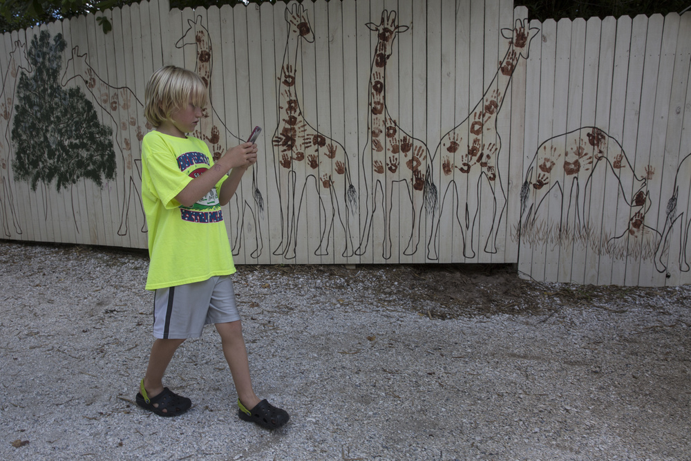 Liam Marshall, 9, of Naples, walks to a Pokémon Go lure spot at the giraffe exhibit in the Naples Zoo on July 15, 2016 in Naples, Florida.