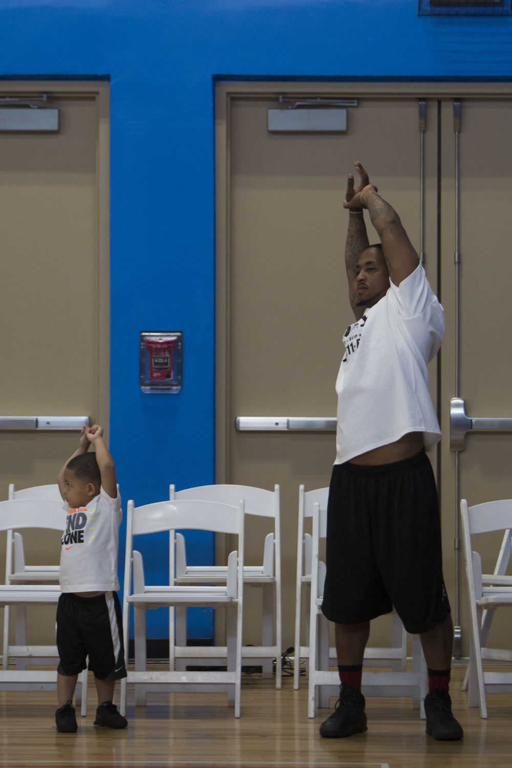 A son copies his dad as he stretches before the 2nd Annual All-Star Basketball Game at the Greater Naples Y.M.C.A. on July 23, 2016 in Naples, Florida.