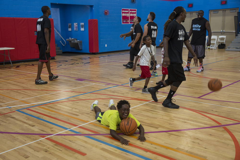Martavion Young, 10, of Naples, laughs on the court while messing around with the players before the 2nd Annual All-Star Basketball Game at the Greater Naples Y.M.C.A. on July 23, 2016 in Naples, Florida.