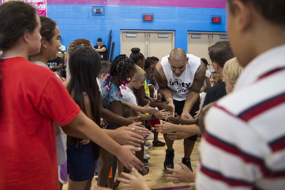 Former NFL defensive end Ikaika Alama-Francis hits kids hands while taking the court for the 2nd Annual All-Star Basketball Game at the Greater Naples Y.M.C.A. on July 23, 2016 in Naples, Florida. The benefit game included two teams with local NFL players Mackensie Alexander, Jayron Kearse, and Makinton Dorleant on two teams titled Team Lee County and Team Collier County.