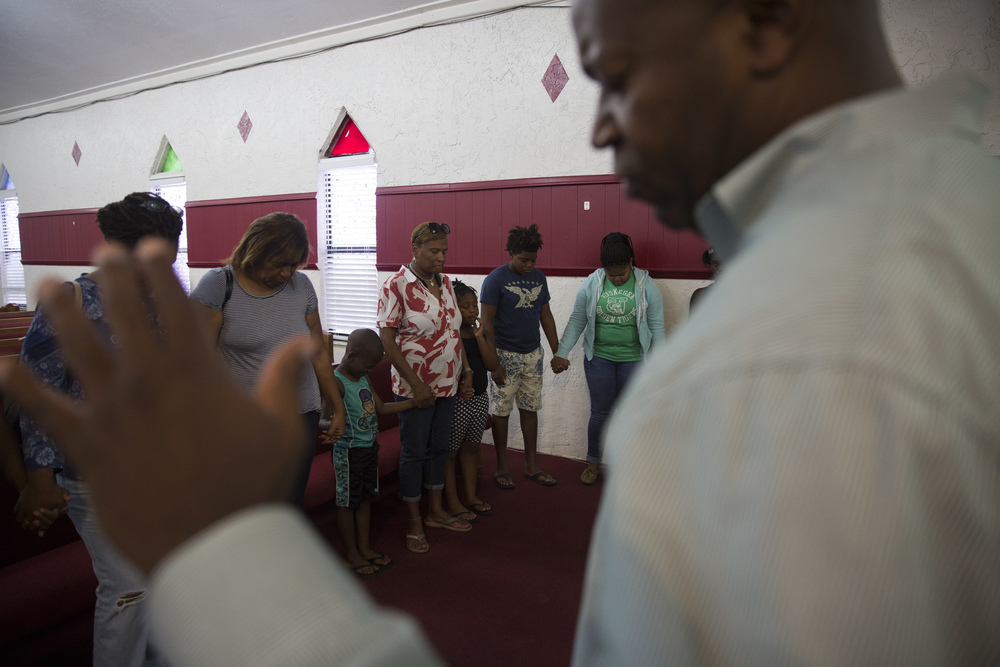 Family and friends hold hands during a prayer at the vigil for Stef'An Strawder at St. Mary's Missionary's Baptist Church on July 25, 2016 in Fort Myers, Florida. Stef'An was killed in a shooting at Club Blu the night before.