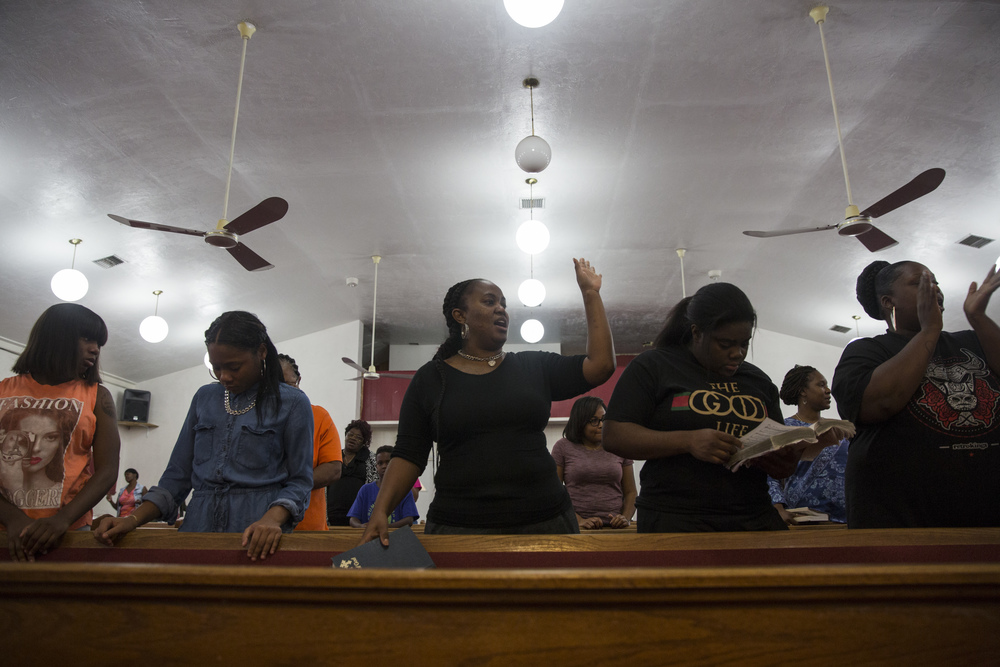 Family and friends sing a hymn during a vigil for Stef'An Strawder at St. Mary's Missionary's Baptist Church on July 25, 2016 in Fort Myers, Florida. Stef'An was killed in a shooting at Club Blu the night before.