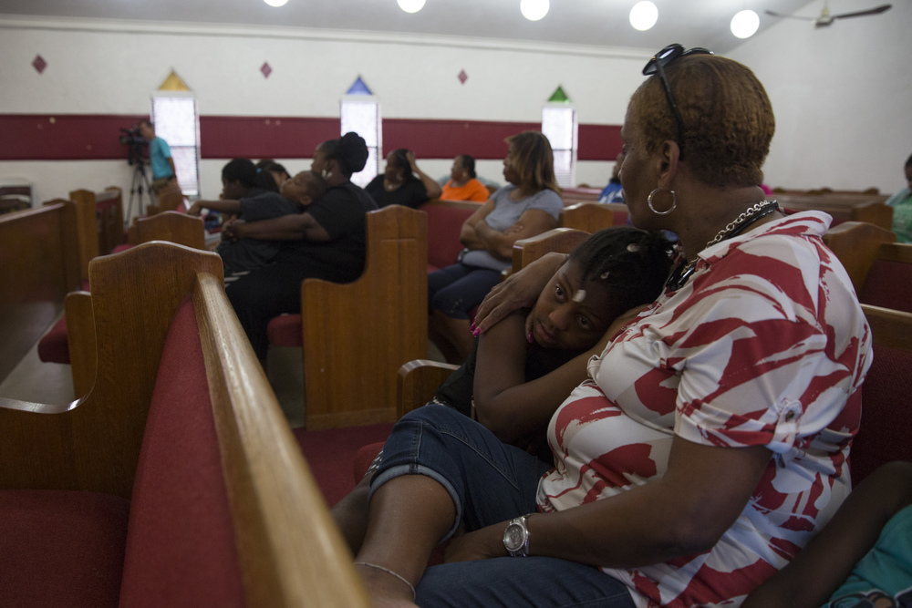 A young girl hugs Michelle Sam as she listens to a speaker during a vigil for Stef'An Strawder at St. Mary's Missionary's Baptist Church on July 25, 2016 in Fort Myers, Florida. Stef'An was killed in a shooting at Club Blu the night before.