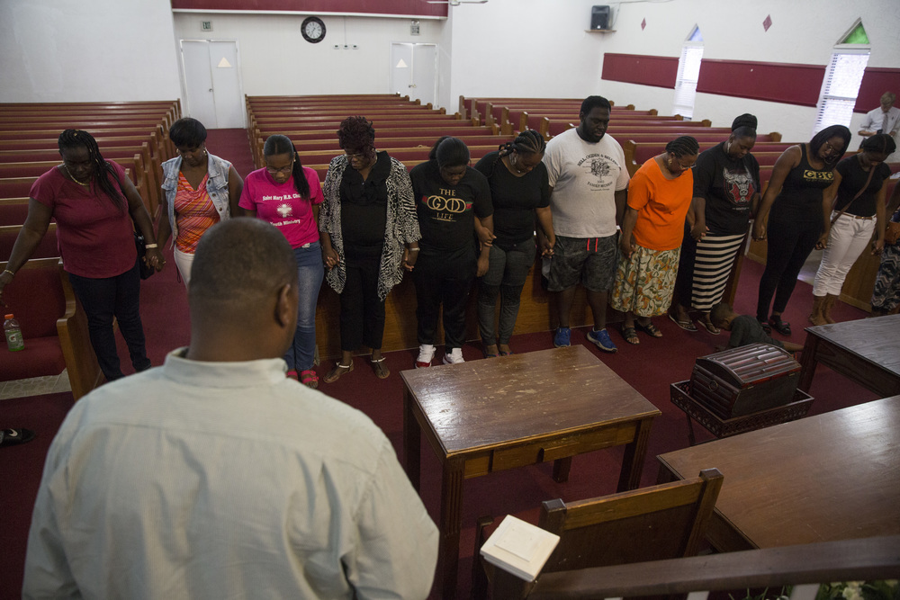 Family and friends bow their heads in prayer during a vigil for Stef'An Strawder at St. Mary's Missionary's Baptist Church on July 25, 2016 in Fort Myers, Florida. Stef'An was killed in a shooting at Club Blu the night before.