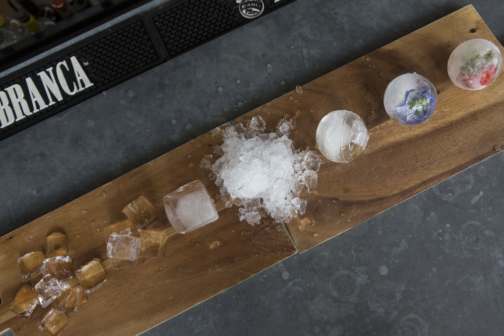 The various types of ice used for cocktails at The Continental include crescent ice, from left, inch and a quarter cube, 2 inch cube, crushed, sphere, an edible pansy sphere and a strawberry sphere. The preparation and use of ice in its various forms can affect cocktails in several ways including dilution, texture, and temperature.