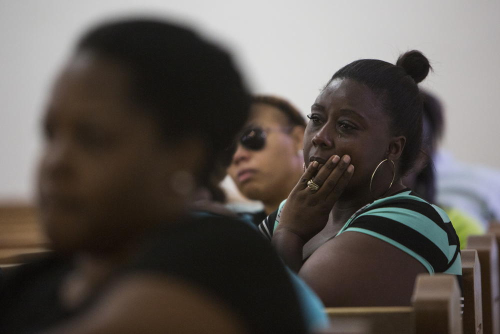 Nicole McMiller, left, listens to another speak during the vigil for Stef'An Strawder at St. Mary's Missionary's Baptist Church on July 25, 2016 in Fort Myers, Florida. Stef'An was killed in a shooting at Club Blu the night before.