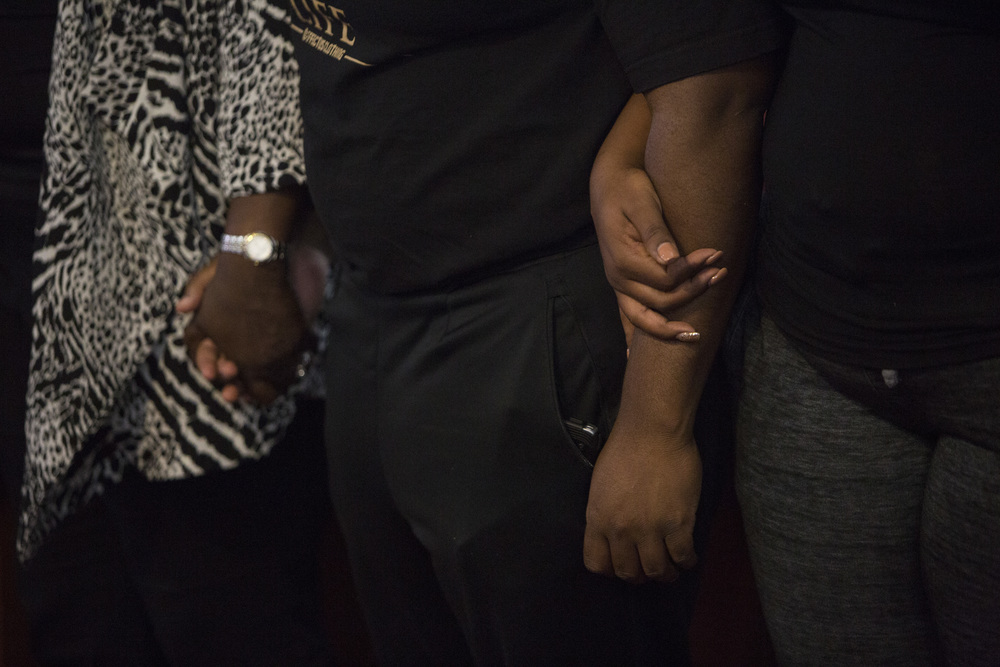 Family and friends hold hands during prayer at the vigil for Stef'An Strawder at St. Mary's Missionary's Baptist Church on July 25, 2016 in Fort Myers, Florida. Stef'An was killed in a shooting at Club Blu the night before.