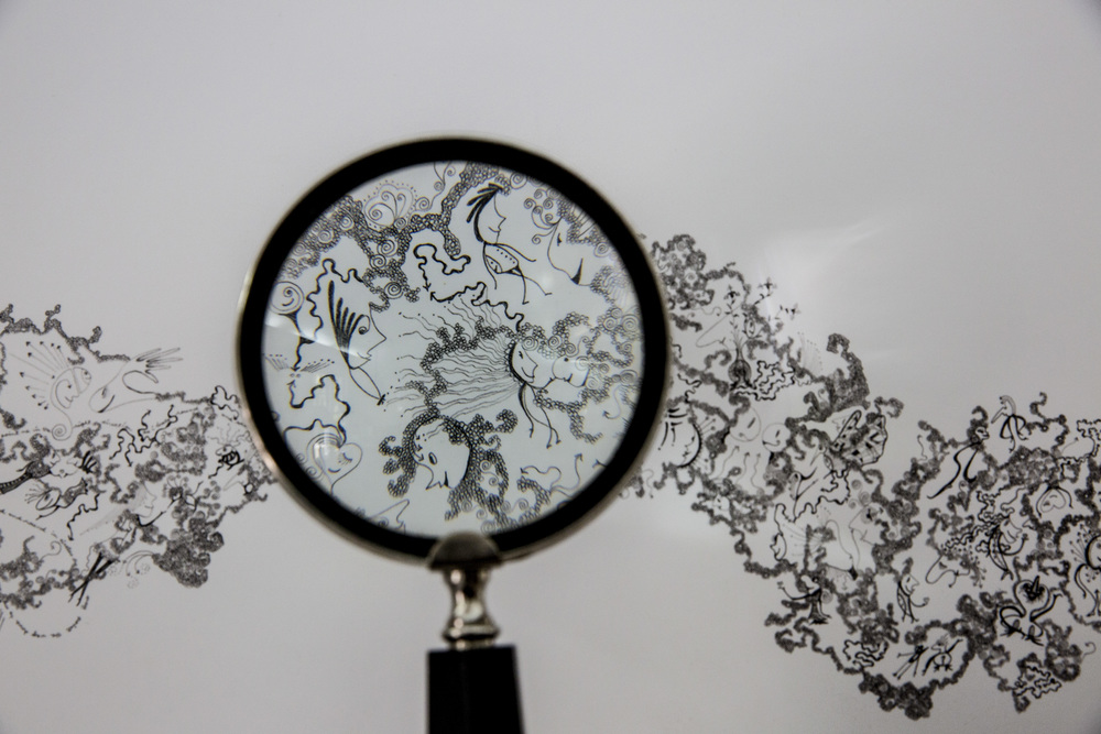 A magnifying glass highlights the intricate detail of a Robin Joy drawing that hangs in her new studio and gallery space in downtown Naples.