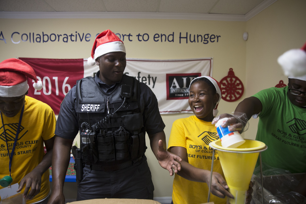 Garelle Charelus, 12, right, laughs while helping package meals of macaroni and cheese during a Meals of Hope event on July 25, 2016 in Naples, Florida. For the Holidays Without Hunger event, around 70-80 kids from the Boys and Girls Club packed meals with members of the Collier County Sheriff's Office while wearing Santa hats and listening to Christmas music.