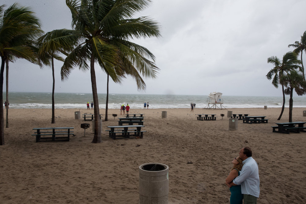 A couple embraces as they watch the storm at Fort Lauderdale Beach, Florida on Thursday, Oct. 6, 2016. Many people were out walking the beach and taking photos to see the storm for themselves.