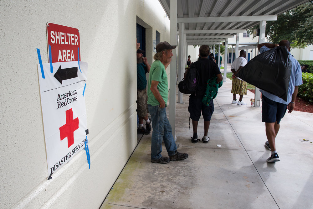 People smoke and wait outside at the Broward County Emergency Shelter set up at Atlantic Technical College with the help of the American Red Cross Disaster Services in Fort Lauderdale, Florida on Thursday, Oct. 06, 2016. As of 10 AM, around 750 people were already checked in to the shelter.