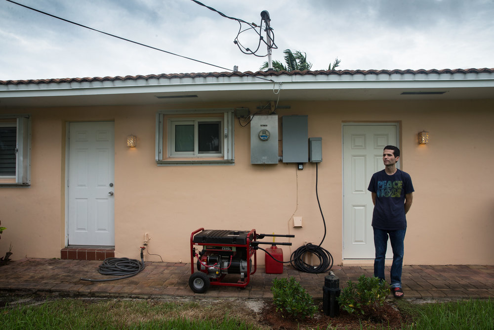 Cristian Seiglie, 44, stands next to the generator powering his home in the Wilton Manors neighborhood of Fort Lauderdale, Florida on Friday, Oct. 7, 2016. He, along with more than 5,000 other customers in Broward County, has been without power since 10:30 PM last night, using a generator this morning for necessities.