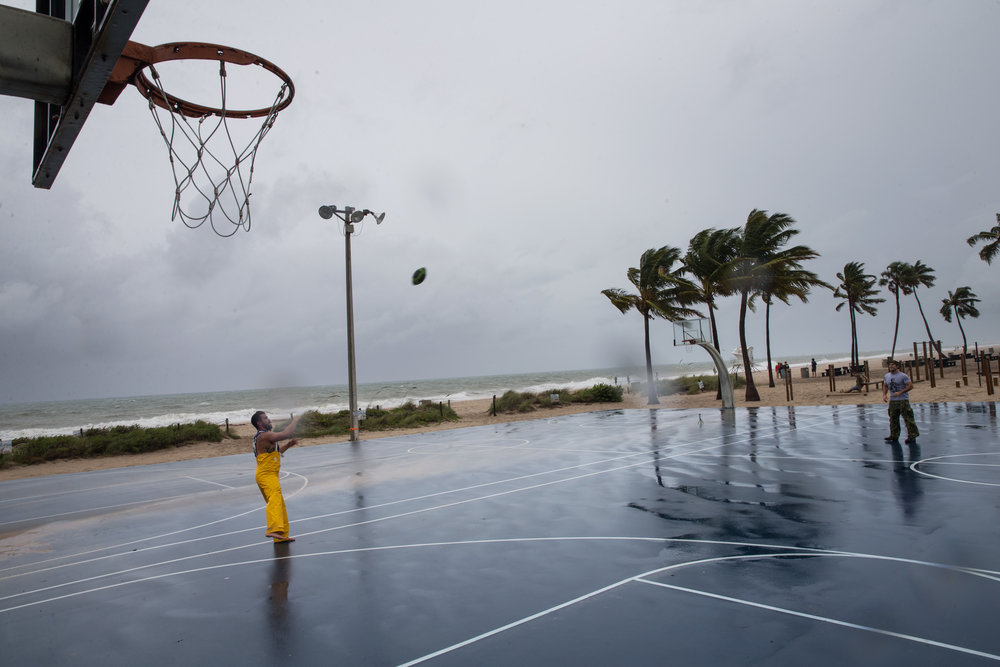 Paul Moran, 25, left, throws the football to Wesley Allen, 28, both from Fort Lauderdale, at Fort Lauderdale Beach, Florida on Thursday, Oct. 6, 2016.