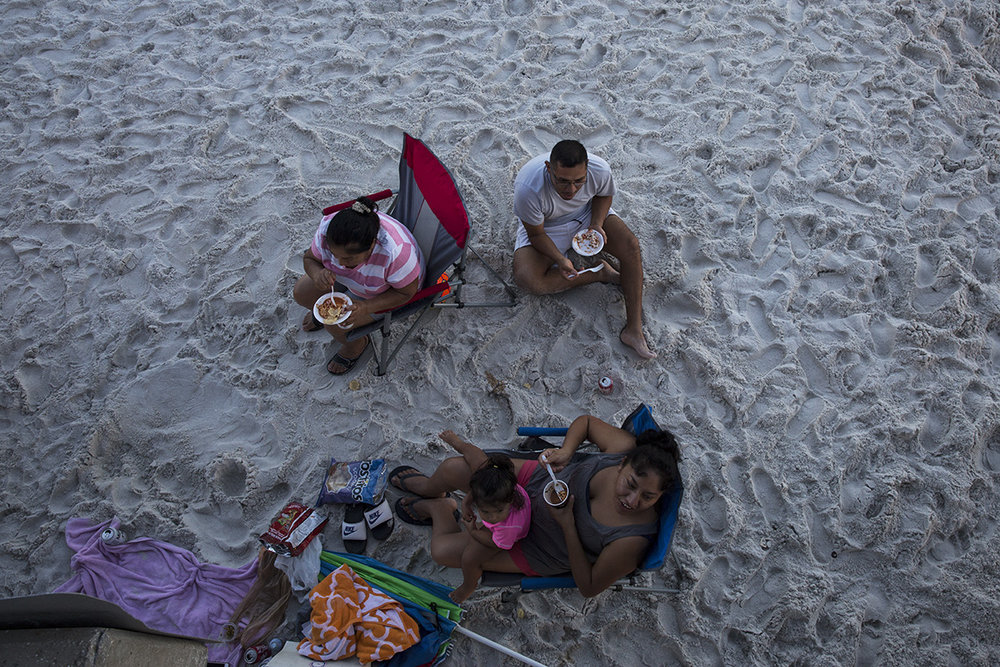A family enjoys dinner on the beach during sunset at the Naples Pier on August 11, 2016.