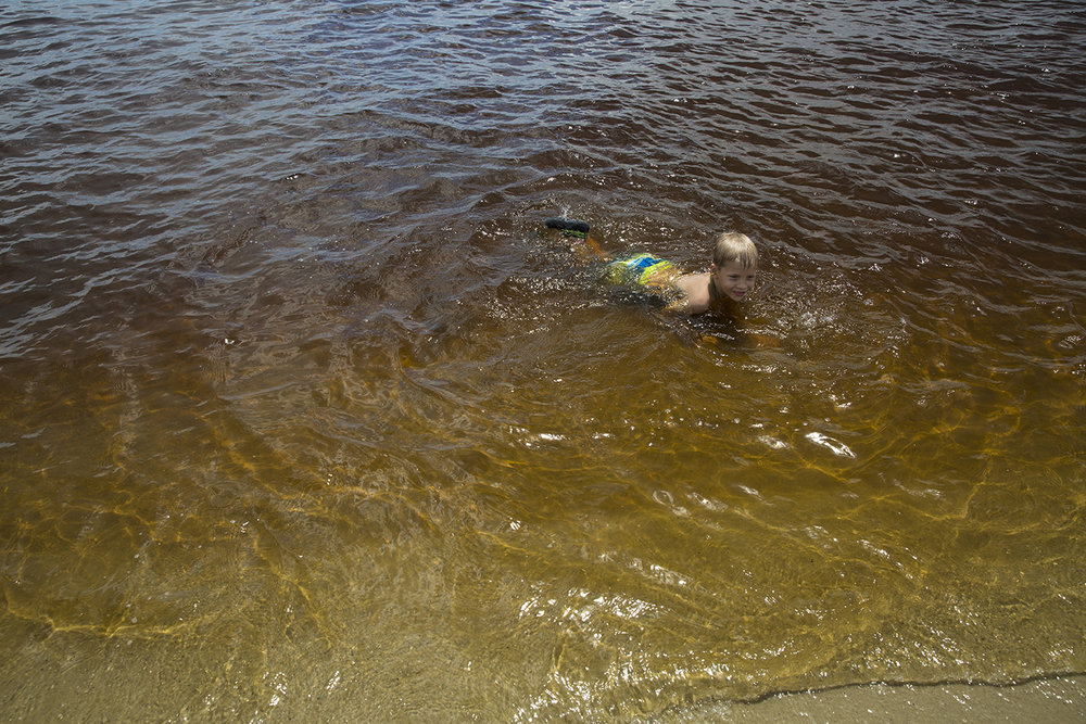 Aiden Garcia, 6, of Lakewood, Colorado, swims in the water at the Cape Coral Yacht Club on August 12, 2016. The beach was reopened to swimmers after being closed due to water quality concerns and its possible health effects on swimmers.