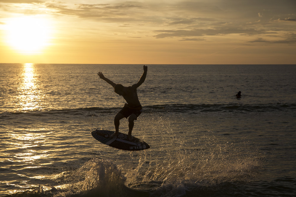 A skim boarder rides the waves during the sunset at the Naples Pier on August 11, 2016.