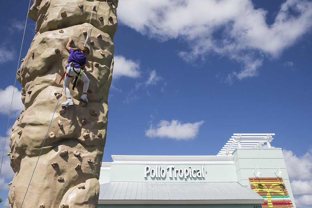 """Gabriella Castro-Davila, 10, climbs the rock wall during the Pollo Tropical Media Cliff Climb Challenge on Friday, Oct. 14, 2016 in Naples, Florida. """"The Boys and Girls Club taught me to never give up,"""" said Gabby. Members of print, radio & TV media climbed the 25 ft rock wall to help raise 200 meals for the Collier County Florida Boys & Girls Clubs after school programs."""