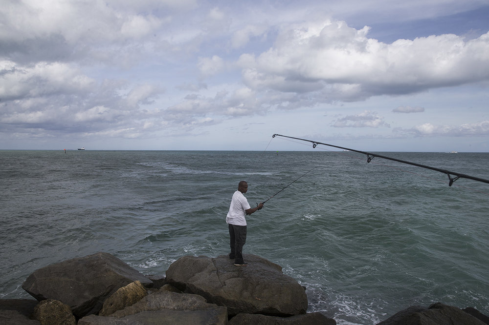 Walter Sanders, of Fort Lauderdale, fishes off the inlet at Port Everglades in Fort Lauderdale, Florida on Friday, Oct. 7, 2016.