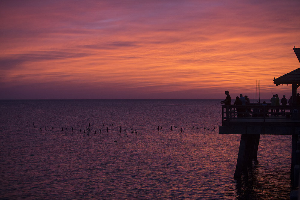 Tourists fish and take in the sunset from the Naples Pier in downtown Naples, Florida on Wednesday, Oct. 26, 2016.