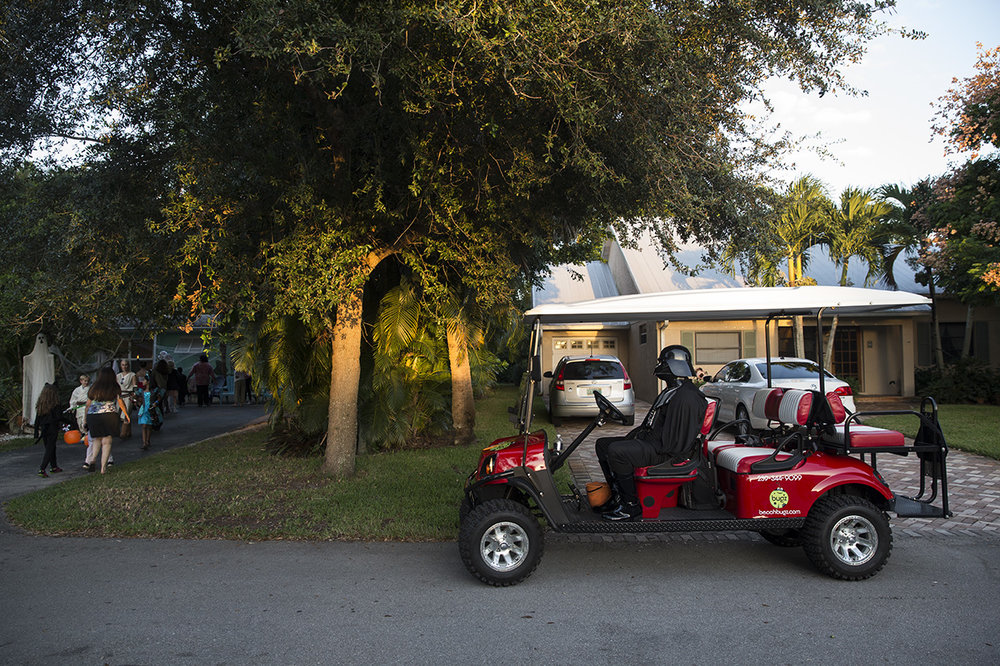 Ryan Acres, dressed as Darth Vader, waits with the golf cart as the rest of his Star Wars themed group trick-or-treats in the Lake Park neighborhood of Naples, Florida on Monday, Oct. 31, 2016.