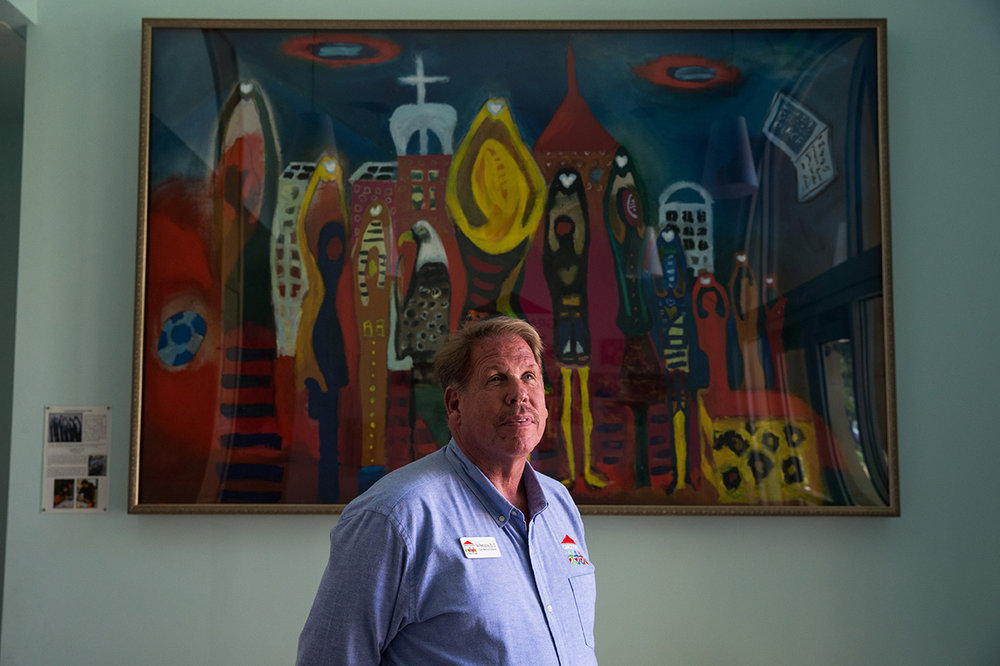 Grace Place for Children and Families Executive Director Tim Ferguson stands in front of a painting inspired by the children of the organization in Naples, Florida on Friday, Oct. 14, 2016. Dr. Ferguson has over 30 years of experience in educational leadership, including service as the founding Principal of Veterans Memorial Elementary School in Naples. Pioneering full-scale family education in Collier County, Grace Place works across the spectrum to break the cycle of poverty.