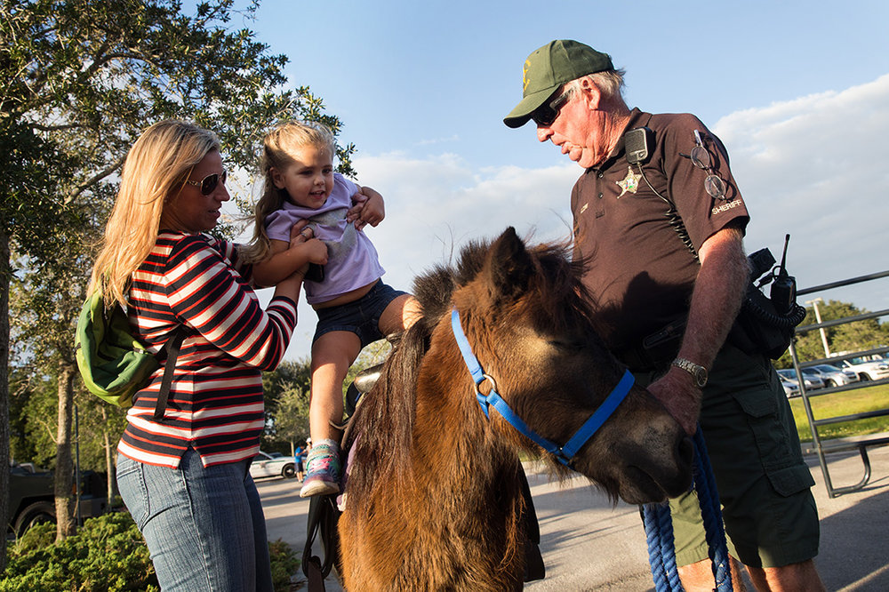 Maggie Harrison, 2, gets lifted onto the pony ride during the Celebrate Safe Communities event at the Vanderbilt Presbyterian Church on Monday, Oct. 10, 2016 in Naples, Florida.