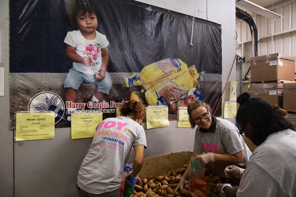 Jussara Campos, 32, of Naples, second from right, laughs at a joke with her co-workers while volunteering at the Harry Chapin Food Bank on Wednesday, Oct. 12, 2016 in Naples, Florida. As a part of Dunkin' Donuts' annual Week of Joy, employee volunteers sorted sweet potatoes into portioned bags to support families struggling with hunger in Southwest Florida.