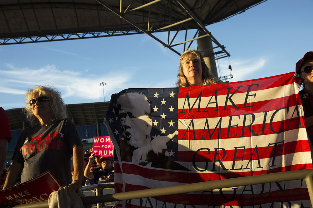 Kerry Pierce, right, of Spring Hill, holds up a Trump flag during a rally for Republican presidential nominee Donald Trump at MIDFLORIDA Credit Union Amphitheater in Tampa, Florida on Monday, Oct. 24, 2016.