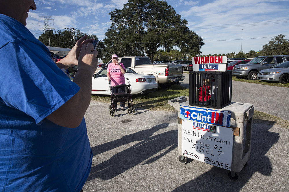 """A man takes a photo of a """"Clinton in Prison"""" display before a rally for Republican presidential nominee Donald Trump at MIDFLORIDA Credit Union Amphitheater in Tampa, Florida on Monday, Oct. 24, 2016."""