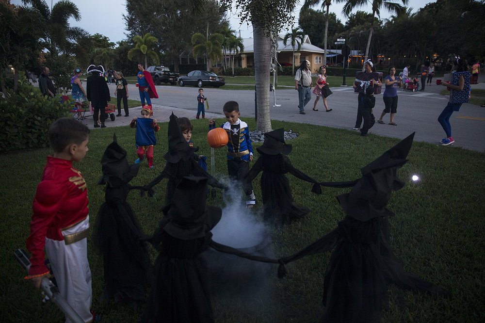 Cruz Garcia, 6, center, dressed as a blue power ranger, inspects a Halloween decoration of a circle of witches while trick-or-treating in the Lake Park neighborhood of Naples, Florida on Monday, Oct. 31, 2016.