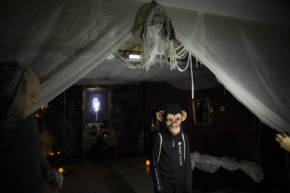 A boy wearing a monkey mask has his photo taken in front of a themed house while trick-or-treating in the Lake Park neighborhood of Naples, Florida on Monday, Oct. 31, 2016.