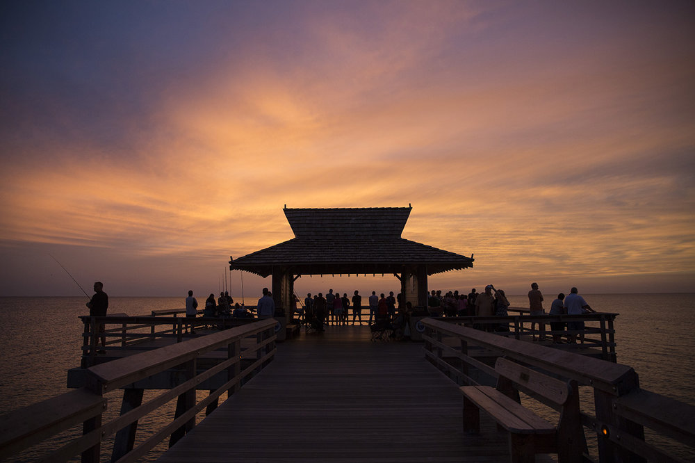 Tourists take in the sunset from the Naples Pier in downtown Naples, Florida on Wednesday, Oct. 26, 2016.