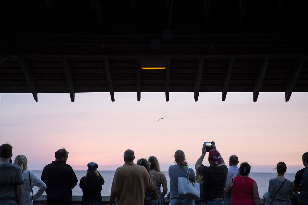 Tourists watch and take photos of the sunset from the Naples Pier in downtown Naples, Florida on Wednesday, Oct. 26, 2016.