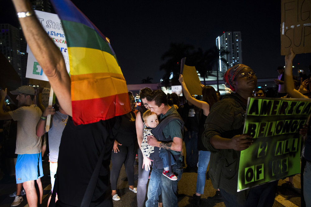 Patrick Griffin, center, kisses his son Patrick Griffin Jr., 18 months, during a non-violent anti-Trump march and protest in downtown Miami, FL on Friday, Nov. 11, 2016. According to one of the group's Facebook pages, the march aimed to warn the people against the dangers of a man like Donald Trump, particularly the encouragement of outspoken hate, racism, anti-islamism, and misogyny.