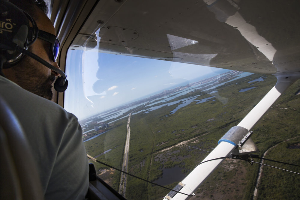 Ian Bartoszek, 40, a science coordinator and wildlife biologist with the Conservancy of Southwest Florida, looks out the window of a plane while tracking Burmese pythons in Collier County using radio telemetry on Monday, March 27, 2017. Male snakes that the team captures are surgically implanted with a radio transmitter, which allows the team to track them across the landscape.
