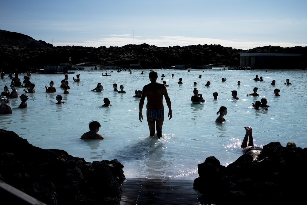 A swimmer enters the Blue Lagoon in Iceland. 2017. The blue colour comes from the natural ingredient silica and the way it reflects sunlight.