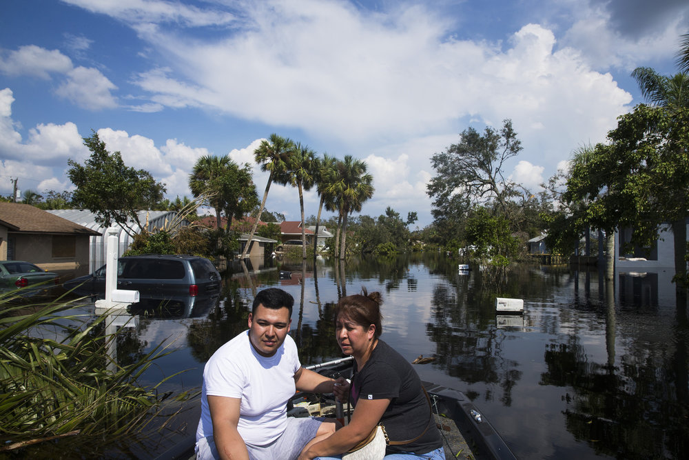 Juan Cardona and his mother Juana Ramirez sit on the bow of a boat as they are ferried across flood waters to check on their home on Saunders Avenue in Bonita Springs on Thursday, Sept. 14, 2017, four days after Hurricane Irma. This was the first time they were able to return to their home after the storm.