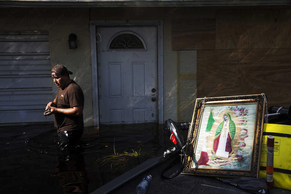 Jose Rangel walks from his home after seeing it for the first time on Chapman Avenue in Bonita Springs on Friday, Sept. 15, 2017, five days after Hurricane Irma. The only things Jose and his roommates took from the house were rosaries and the photo of Our Lady of Guadalupe.