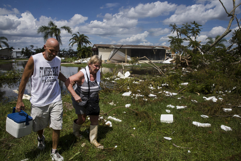 Dave Stroshein helps his wife Linda through the flood water and debris at Citrus Park in Bonita Springs on Wednesday, Sept. 13, 2017, three days after Hurricane Irma. The Stroshein's came back to check on their home for the first time since the storm, which was luckily still standing.