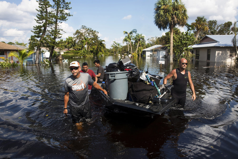 Don Manley, left, and Pedro Castellano, right, pull Manley's boat, loaded with resident's belongings, along a flooded Chapman Avenue in Bonita Springs on Friday, Sept. 15, 2017, five days after Hurricane Irma.