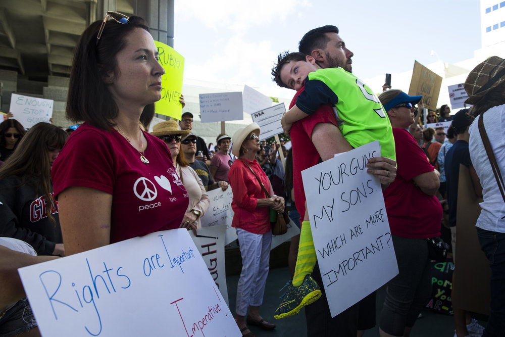 Brittnie Rowan, left, listens to speakers while Shawn McAskill holds their son, Ethan McAskill, a 5-year-old kindergarten student, during a gun control rally in front of the federal courthouse in Fort Lauderdale, Fla. on Saturday, Feb. 17, 2018. Students, community members, elected officials and gun control advocates gathered together to call for common sense gun laws and firearm safety legislation in the wake of the school shooting that left 17 people dead and 15 others injured this past Wednesday in Parkland, Fla.