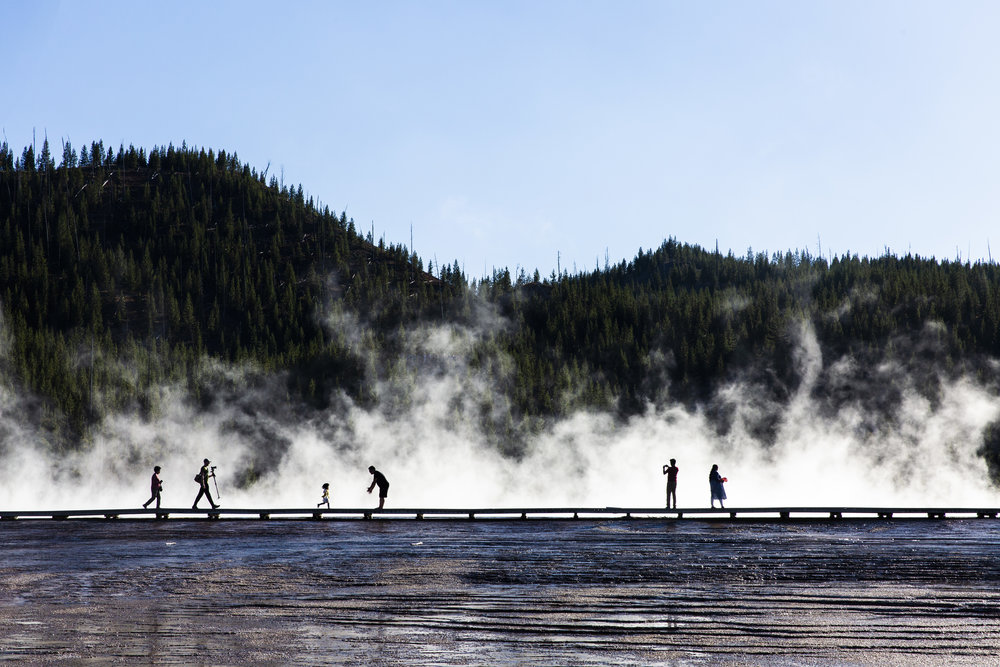 Tourists walk around the Grand Prismatic Hot Spring at Yellowstone National Park's Midway Geyser Basin in Wyoming. 2018